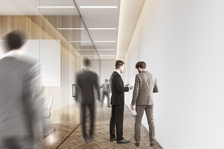 boardroom: Rear view of men in suits in the company corridor. They are talking or walking to their workplaces. 3d rendering. Mock up.