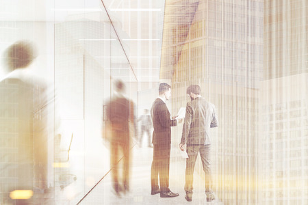 double exposure: Rear view of men in suits in the company corridor. They are talking or walking to their workplaces. 3d rendering.  Toned image. Double exposure Stock Photo