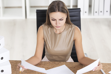 Portrait of a woman in beige at her cork table looking at two documents and looking for a deference. Stock Photo