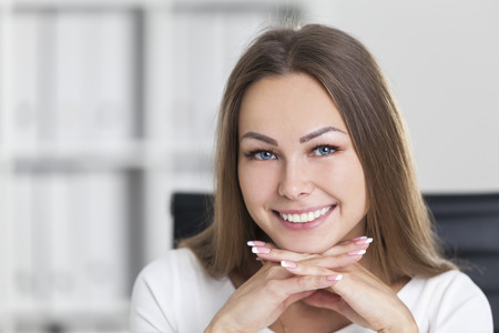 chin on hands: Close up of a cheerful businesswoman smiling broadly and looking at the viewer. She has her hands under her chin. Concept of satisfaction. Stock Photo