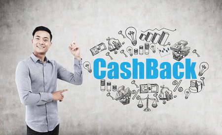 repossessing: Portrait of an Asian man standing with a finger in the air near a concrete wall with a blue cash back drawing on it. Stock Photo