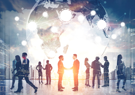 Silhouettes of business people shaking hands and walking against a morning cityscape. There is a world map and a network.