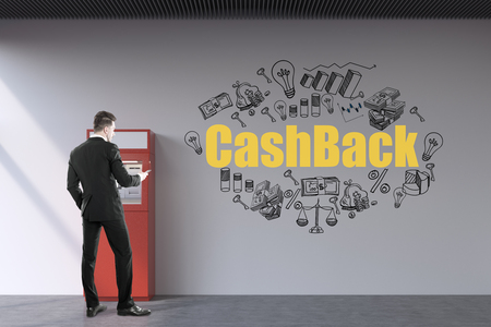 withdrawing: Rear view of a bearded businessman wearing a black suit who is withdrawing money from a red atm machine. There is a yellow cash back sketch on the wall.
