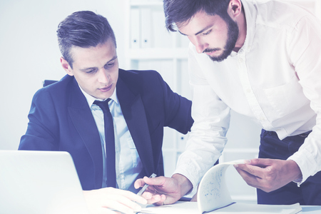 Portrait of two young and busy businessmen working together. One is standing and writing. The second is dictating the words. Toned image. Film effect Stock Photo