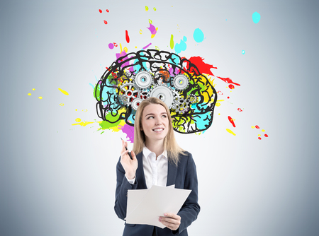 Portrait of a blond woman with a stack of documents standding near a gray wall with a colorful and bright brain with gears inside it.