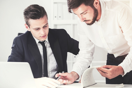 Portrait of two young and busy businessmen working together. One is standing and writing. The second is dictating the words. Toned image.