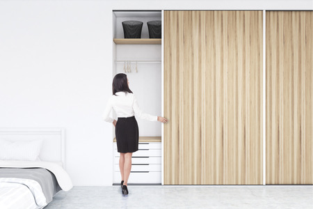 Rear view of a woman standing near a built in wooden wadrobe in a room with hangers and boxes, a set of drawers is in the lower part. There is a double bed to the left. 3d rendering, mock up