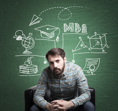 Portrait of a bearded businessman wearing a checkered shirt and sitting near a green chalkboard with an education sketch on it.