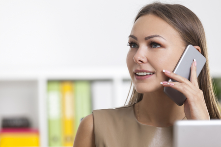 Close up of a young blond businesswoman on her phone in an office with colorful green, yellow and white binders. Concept of communication.