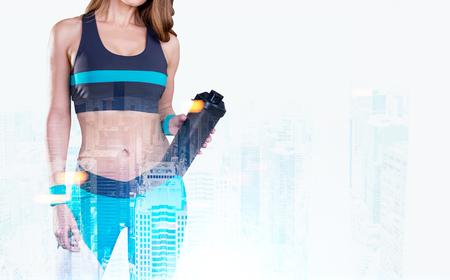unrecognizable: Close up portrait of a woman with a yoga mat wearing a blue and black sportswear and standing against a foggy cityscape. Toned image, double exposure, mock up