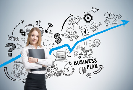 Portrait of a smiling businesswoman holding a folder and standing near a gray wall with a blue graph and business plan icons on it. Stock Photo