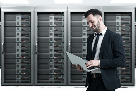 Side view of a man holding his laptop while standing in a server room with four large servers. Concept of IT work. Stock Photo