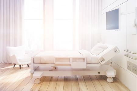 Vista lateral de una sala de hospital con una cama, un televisor, un sillón blanco y cortinas en grandes ventanales. Representación 3d, se burlan hasta. Imagen entonada