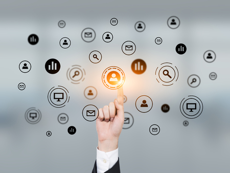 glassboard: Close up of a hand of a businessman with a glowing finger pointing at one of the network icons on a glassboard. Stock Photo