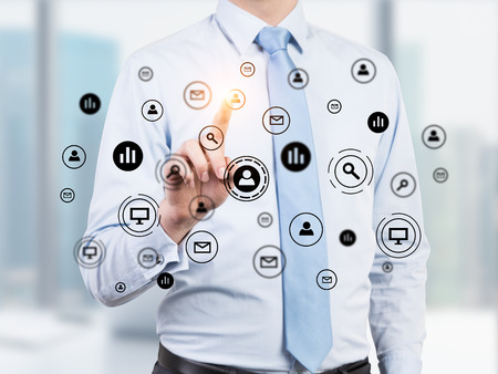 glassboard: Close up of a businessman wearing a blue shirt and tie and pointing at one of the business network icons on a glassboard.