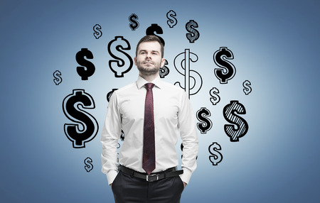 Confident businessman with his hands in the pockets is standing near a blue wall with dollar signs on it. Stock Photo