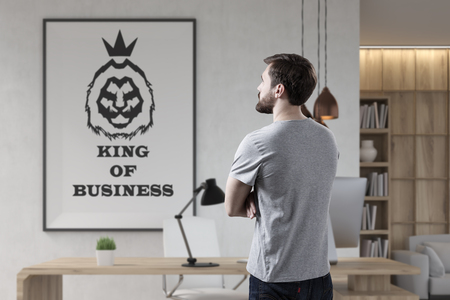 Rear view of a bearded young businessman wearing a gray T-shirt and looking at a king of business poster on an office wall. Stock Photo