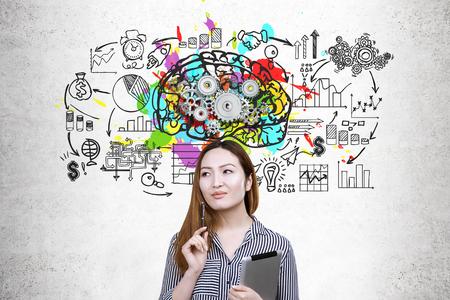 Porträt einer Asain-Geschäftsfrau, die eine Tablette hält und nahe einer Betonmauer mit einem Gehirn mit Gangskizze auf ihr steht.