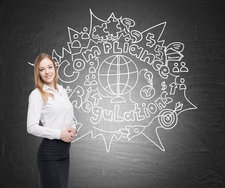 Portrait of a smiling blond businesswoman standing near a blackboard with compliance and regulations sketch on it. Imagens - 74133930