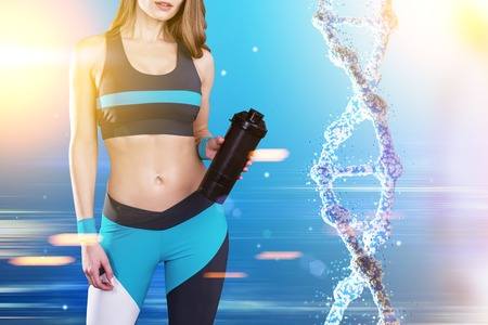 Close up of a sportswoman wearing a blue, black and white sportswear and standing against blue background with a dna to her right. Toned image. Archivio Fotografico