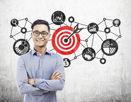 Portrait of an Asian businessman wearing glasses and standing with crossed arms near a target sketch on concrete. Stockfoto