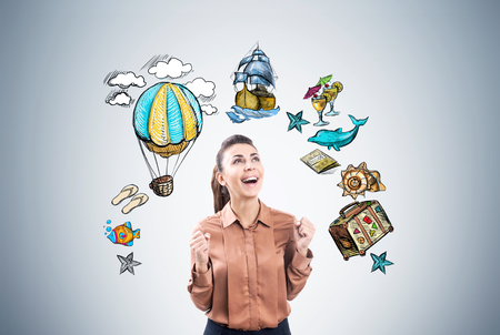 Portrait of a happy businesswoman in brown screaming with joy near a gray wll with travel sketches drawn on it. Stock Photo