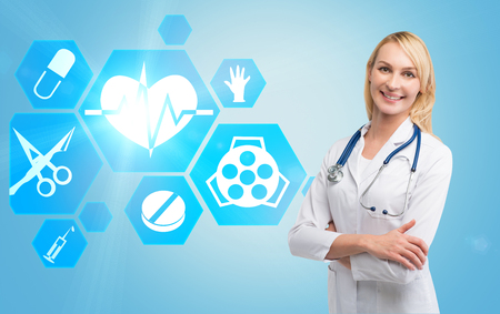 Portrait of a young smiling woman doctor standing against a blue background with hexagonal medicine icons to the side of her.