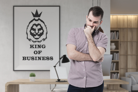 Portrait of a bearded young businessman wearing a pink shirt and standing in an office with a king of business poster on the wall.