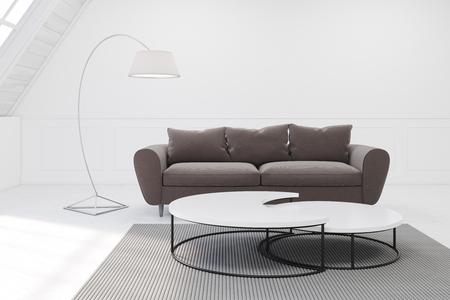 #74291970   Ein Graues Sofa Und Ein Tisch Stehen In Einem Zimmer Auf Dem  Dachboden. Es Gibt Einen Schmalen Runden Tisch Und Einen Teppich.