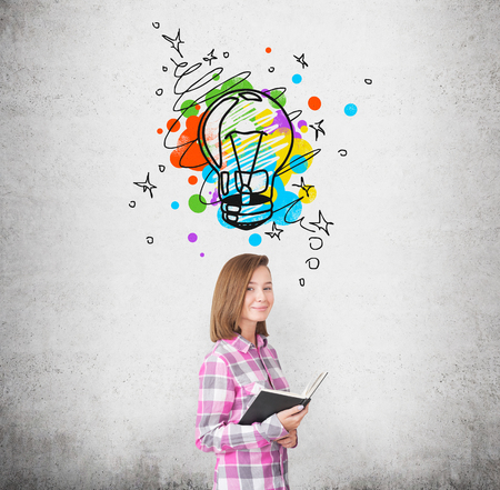 Portrait of a young woman wearing a pink checkered shirt and standing near a concrete wall with a colorful light bulb drawn above her head. Stock Photo