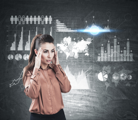 Portrait of a stressed woman wearing a brown blouse and standing near a chalkboard with graphs. Elements of this image furnished by NASA Stock Photo