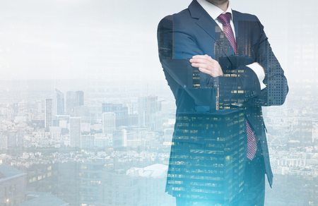 Close up of an unrecognizable man in a suit standing with his arms crossed against a city panorama. Double exposure. Toned image Stock Photo