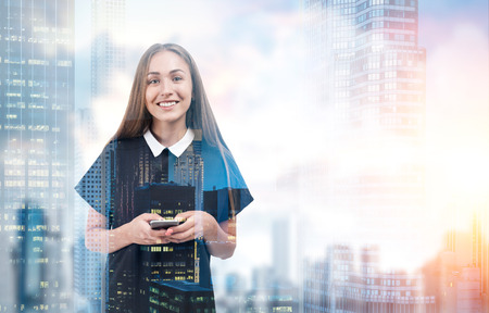 Portrait of a blond businesswoman standing with her smartphone against a foggy city panorama. Toned image. Mock up. Double exposure.