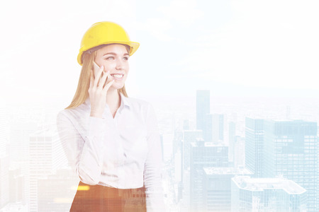 employe: Portrait of a blond woman in a yellow hardhat talking on her smartphone while standing against a city panorma. Toned image