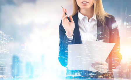 Close up portrait of a blond businesswoman standing with her papers and a pen against a city panorama. Toned image. Mock up. Double exposure. Stock Photo