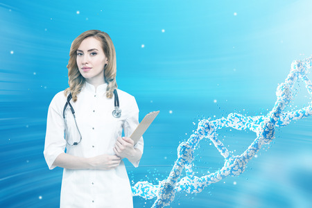Portrait of a red haired woman doctor holding her clipboard and standing against a blue background with a large dna chain. Stock Photo