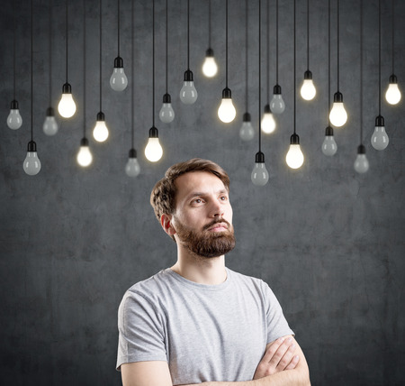 bearded wires: Portrait of a bearded man wearing a gray T-shirt and standing with crossed arms near a blackboard with bulbs on wires hanging in front of it. Stock Photo