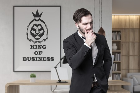 Portrait of a bearded young businessman wearing a dark suit and standing in an office with a king of business poster on the wall.