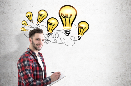 bearded wire: Side view of a young bearded guy holding a notebook while standing near a concrete wall with many light bulb connected with a wire. Stock Photo