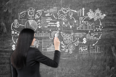 schemes: Rear view of a businesswoman with black hair drawing a business scheme on a blackboard in front of her.