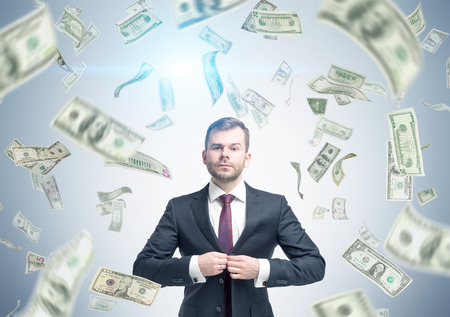 Portrait of a bearded businessman buttoning his suit while standing under a dollar rain. Concept of good money investment. Stock Photo