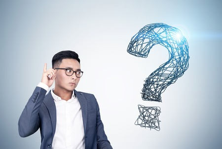 Portrait of an Asian buisnessman wearing glasses and standing near a gray wall with a shining question mark drawn on it. Stock Photo