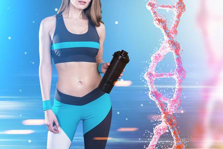 Primo piano di una sportiva indossando un abbigliamento sportivo blu, bianco e nero e in piedi contro sfondo blu, con una catena di DNA alla sua destra. Immagine tonica. Archivio Fotografico - 74636776