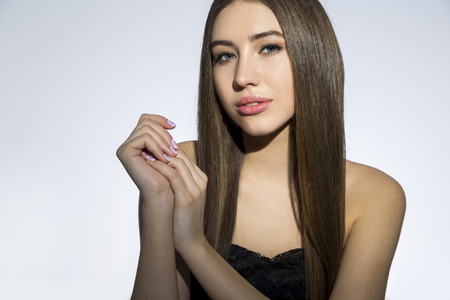 Front view of a thoughtful woman with full lips and long brown hair sitting against a gray wall. Mock up.