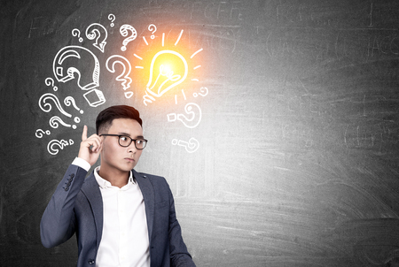 business mind: Portrait of an Asian businessman standing near a blackboard with a light bulb and question marks drawn on it. Mock up