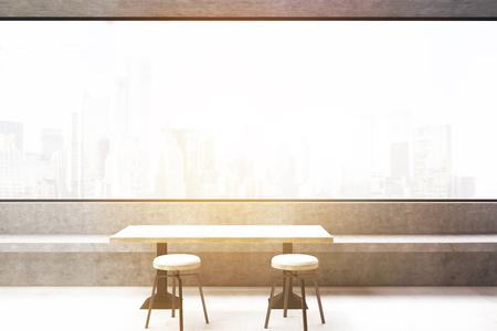 Cafe con una finestra panoramica con vista sulla città e sgabelli in
