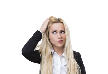 Isolated portrait of a confused pretty and young blond woman scratching her head. She is wearing a business suit and a white shirt.