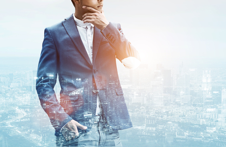 Close up of an unrecognizable businessman in a suit rubbing his chin while satanding against a city panorama. Double exposure
