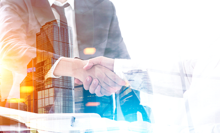 Close up of two business partners shaking hands at a table. There is a sunny city panorama in the foreground. Toned image, double exposure. Archivio Fotografico