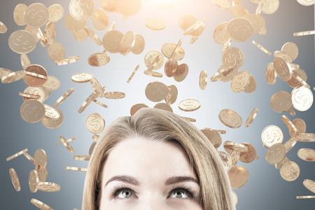 Close up of a head of a blond businesswoman standing near a gray wall under a coin dollar rain. Toned image. Stock Photo